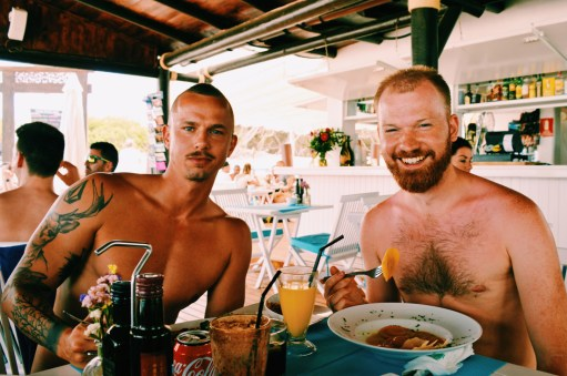 Ibiza Gay Travel Tips Gay Travel Ibiza Beefy compnay! Daan and his vegetarian lunch at Chiringay | Gay Couple Travel Gay Beach Ibiza Town Spain © CoupleofMen.com