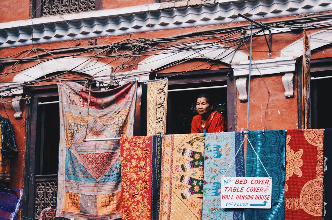 Old woman overlocking the busy market in Kathmandu | Gay Travel Nepal Photo Story Himalayas © Coupleofmen.com