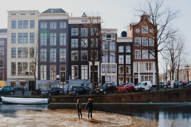 Gay Couple Travel Blogger Hand-in-hand on the ice of the Keizersgracht | Amsterdam Frozen Canals © Coupleofmen.com