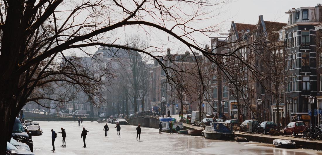 Winter on Amsterdam's frozen Canals Winter Amsterdam Netherlands Frozen Prinsengracht Canal Ice Ice-Skaters on the frozen Prinsengracht in March 2018 © Coupleofmen.com