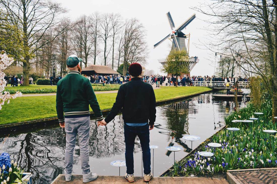 Gay Travel bloggers Couple of Men hand-hand Tulip fields, a windmill, and two gay men hand-in-hand: See you soon! | Keukenhof Tulip Blossom Holland © Coupleofmen.com