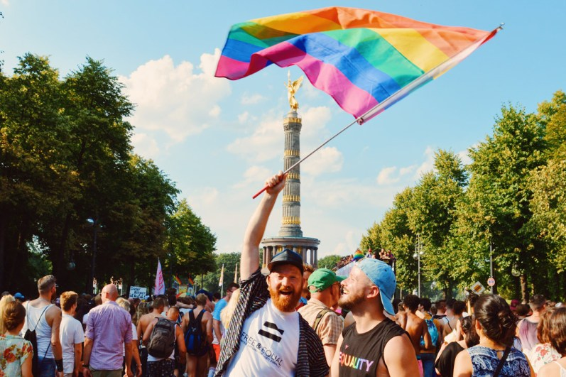 Happy Pride - Couple of Men waving the Rainbow Flag over the Victory Column together | CSD Berlin Gay Pride 2018 © Coupleofmen.com