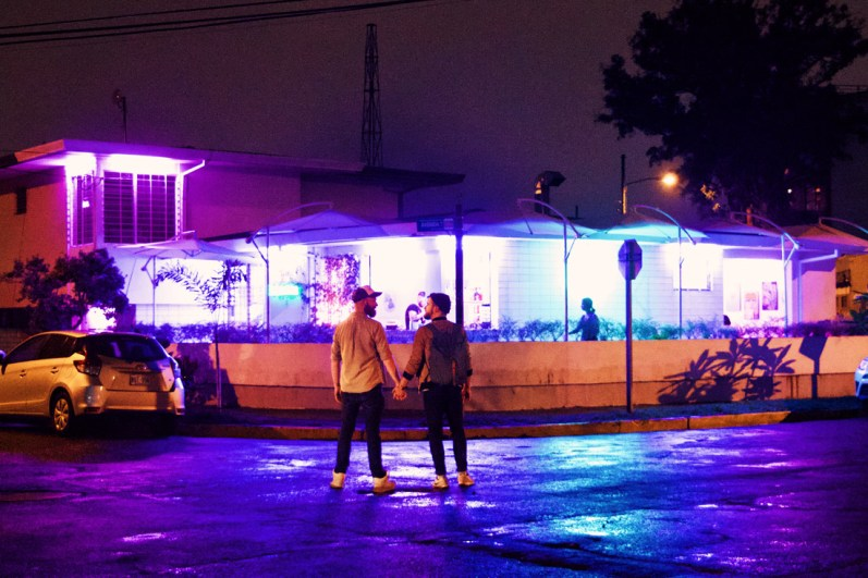 Hand-in-hand in front of the Neon Ice sign, our favorite gay bar in San José | Gay-friendly Costa Rica © Coupleofmen.com