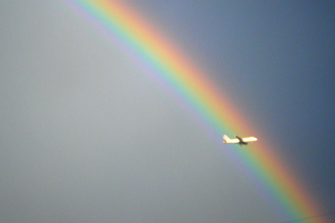 Ein Flugzeug vor einem knallig bunten Regenbogen | US Airlines Gender Neutral Buchungsoption © Coupleofmen.com