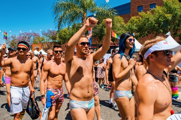 Gay swim team for some extra sexy fun on the streets of Los Angeles California. Half naked guys in swim wear demonstrating and dancing during LA Pride 2019© Coupleofmen.com