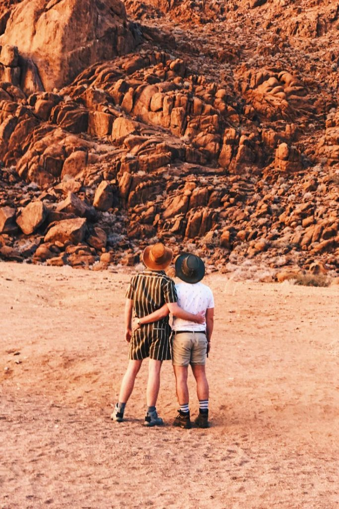 Arm in arm enjoying the beauty of the red rock formation during our first Sossusvlei Lodge Nature Drive © Coupleofmen.com