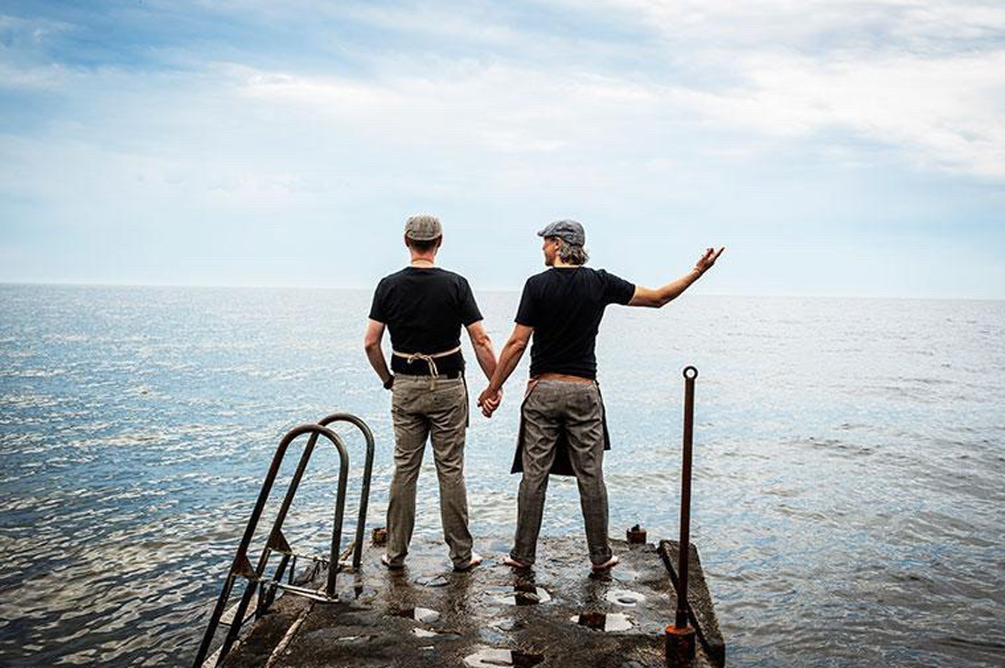 two gay men hand in hand looking over the baltic sea in Sweden Hand in Hand into a great future together - © Café Ransvik Havsveranda