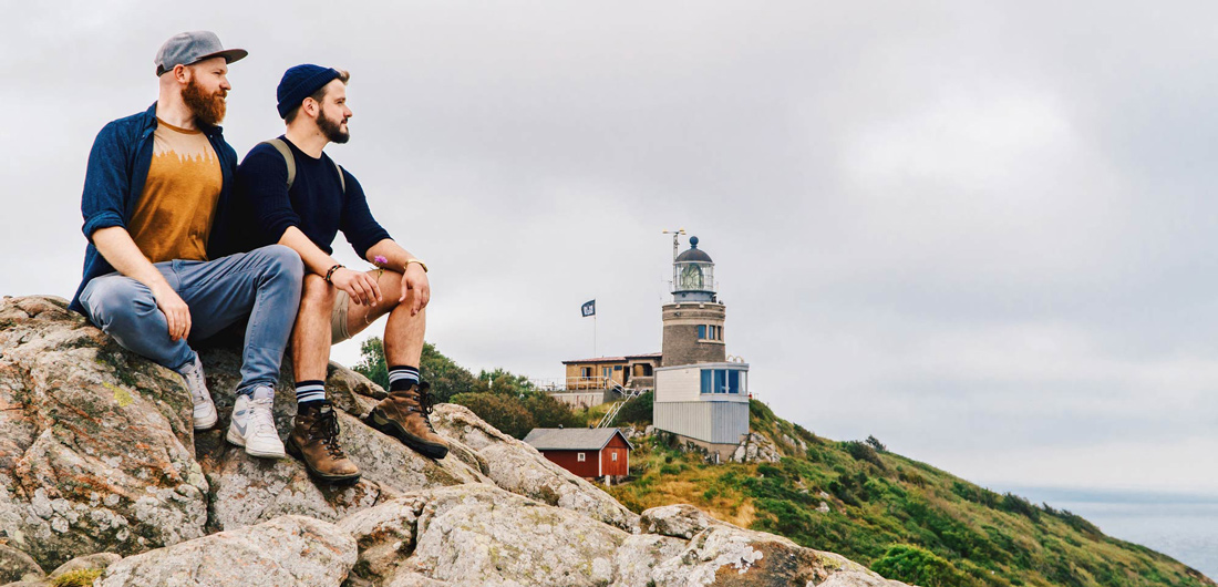 Gay Summer Road Trip Skåne Enjoying the view of the rough coast at Kullaberg with Kullens Lighthouse in the background © Coupleofmen.com