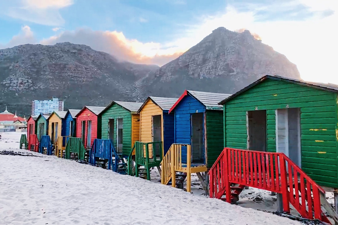 The world-famous colored beach houses of Muizenberg Beach in front of the Muizenberg Mountains © Coupleofmen.com