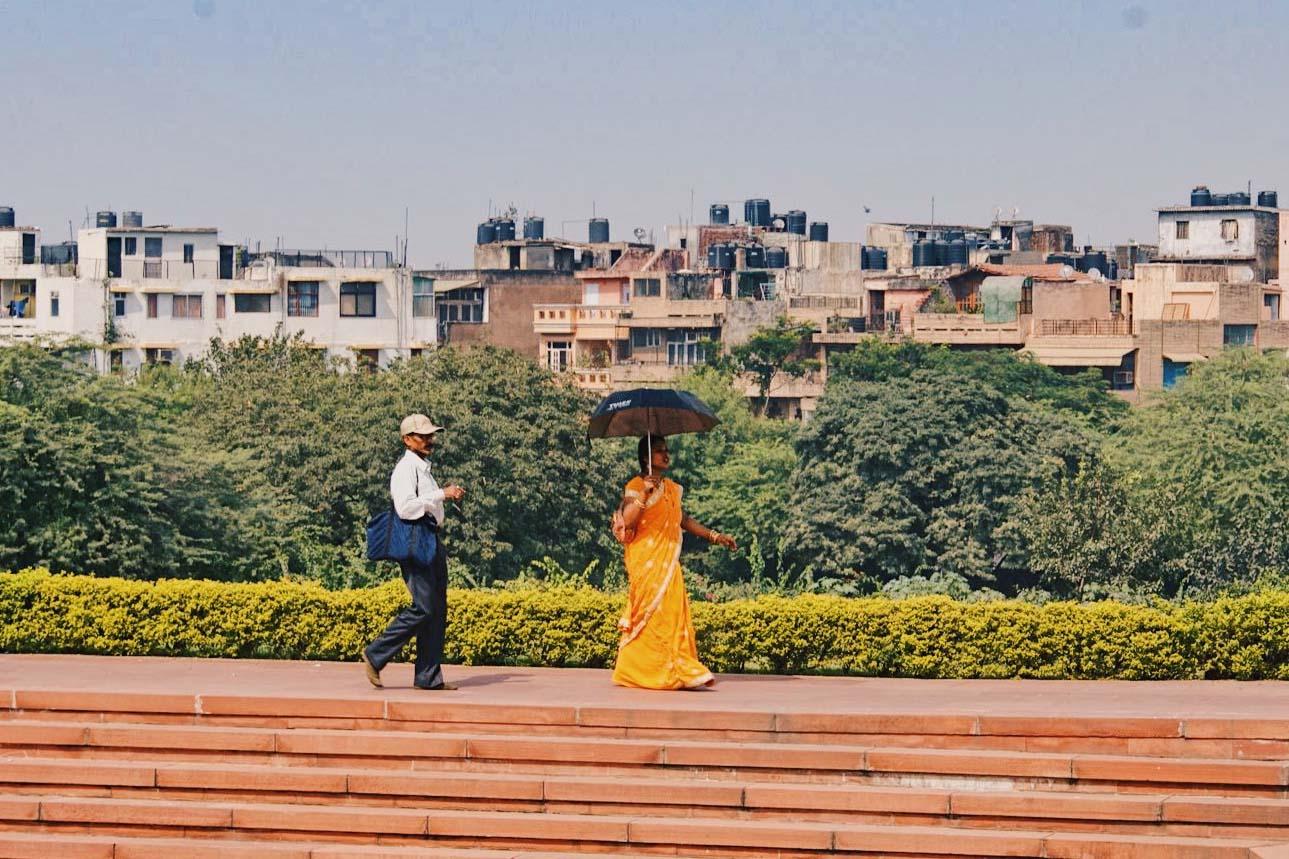 Gay Reise Indien Lotus Temple in New Delhi and an orange dressed woman with black umbrella © Coupleofmen.com