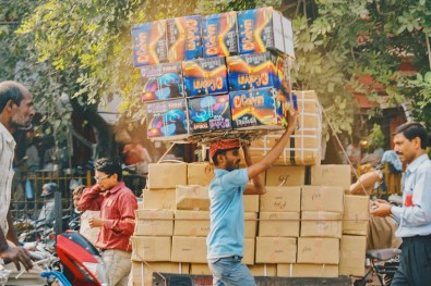 Streetlife in New Delhi with a man carrying boxes on his head © Coupleofmen.com