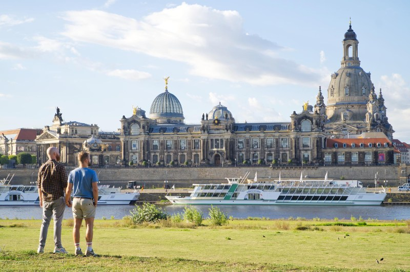 A Gay Couple hand-in-hand looking at the Dresden-Panorama and the River Elbe © Coupleofmen.com