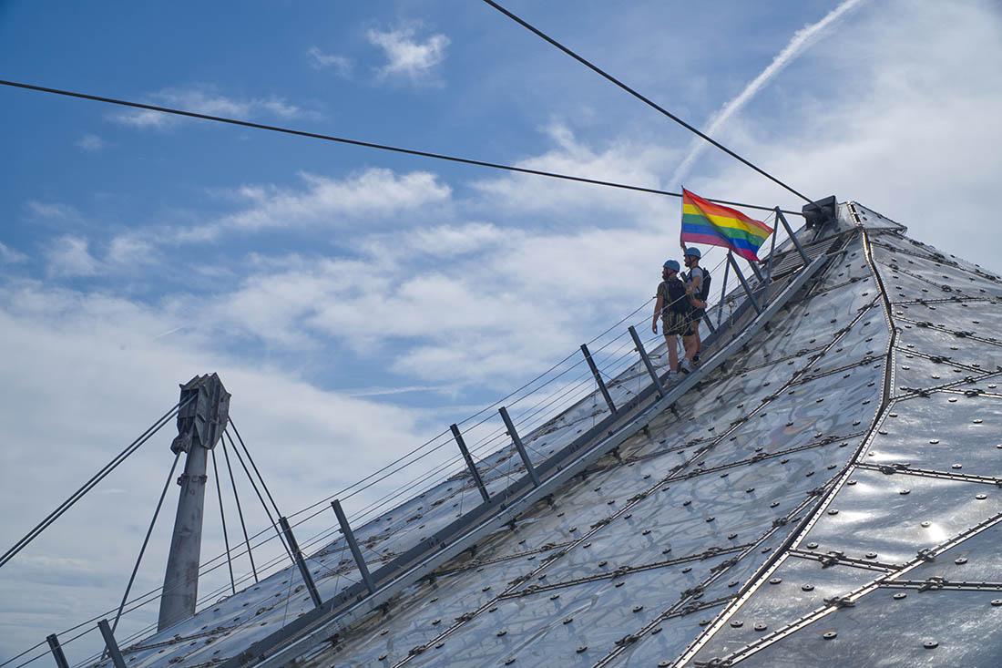 Munich Gay City Trip Proudly waving the flag on the rooftop of the Olympic Stadium from 1972 © Coupleofmen.com