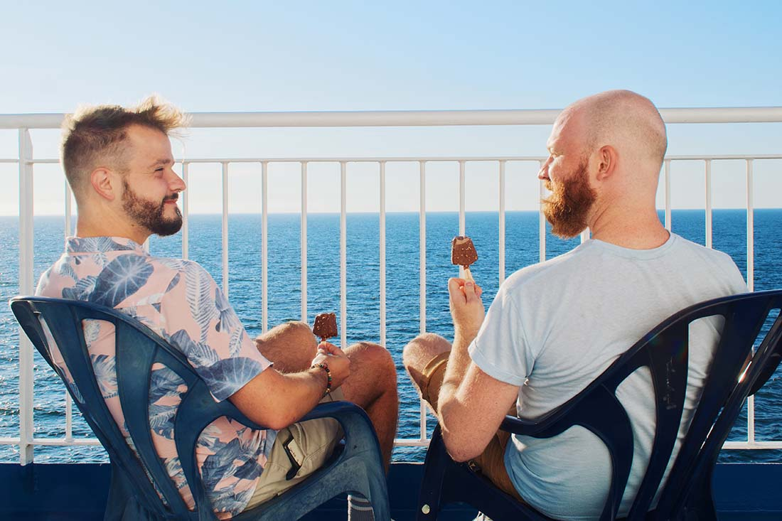 A bearded Gay couple having an ice cream break from driving on the TT-Line ferry boat to Sweden © Coupleofmen.com