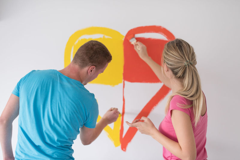 73276655 - young happy couple are painting a heart on the wall while doing repair at home.