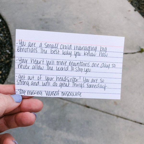 A girl holding a notecard with a letter she wrote to herself