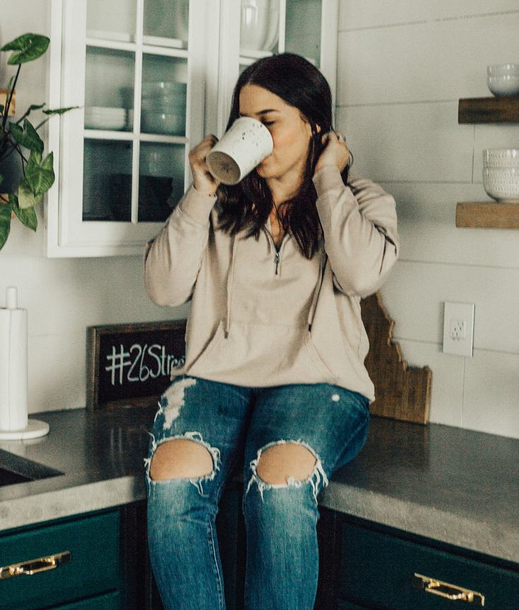 Tara Bixby of courageously.u sipping coffee on the counter while holding her hair back