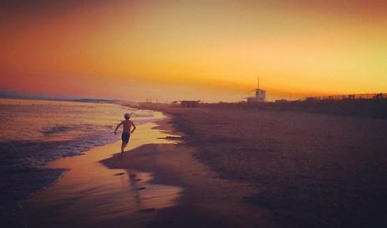 Enfant courant sur la plage avec un magnifique coucher de soleil