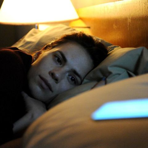 Person in bed, staring at a lit-up cell phone on the pillow
