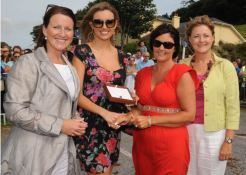 """LADY IN RED: Angela O'Donovan, Timoleague (second from left) winner of the """"Best Dresed Ladt Competition"""" at the Courtmacsherry Strand Races receives her prize from former Miss World, Rosanna Davidson. Also included are judges, Colette Flynn (left) and Mary Madden. Photo: Martin Walsh."""