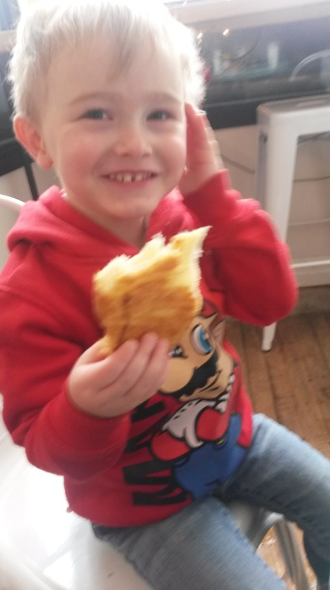 A happy little Boy#2 eating a croisant and laughing at Paul dancing his Baby yoshi toy around.
