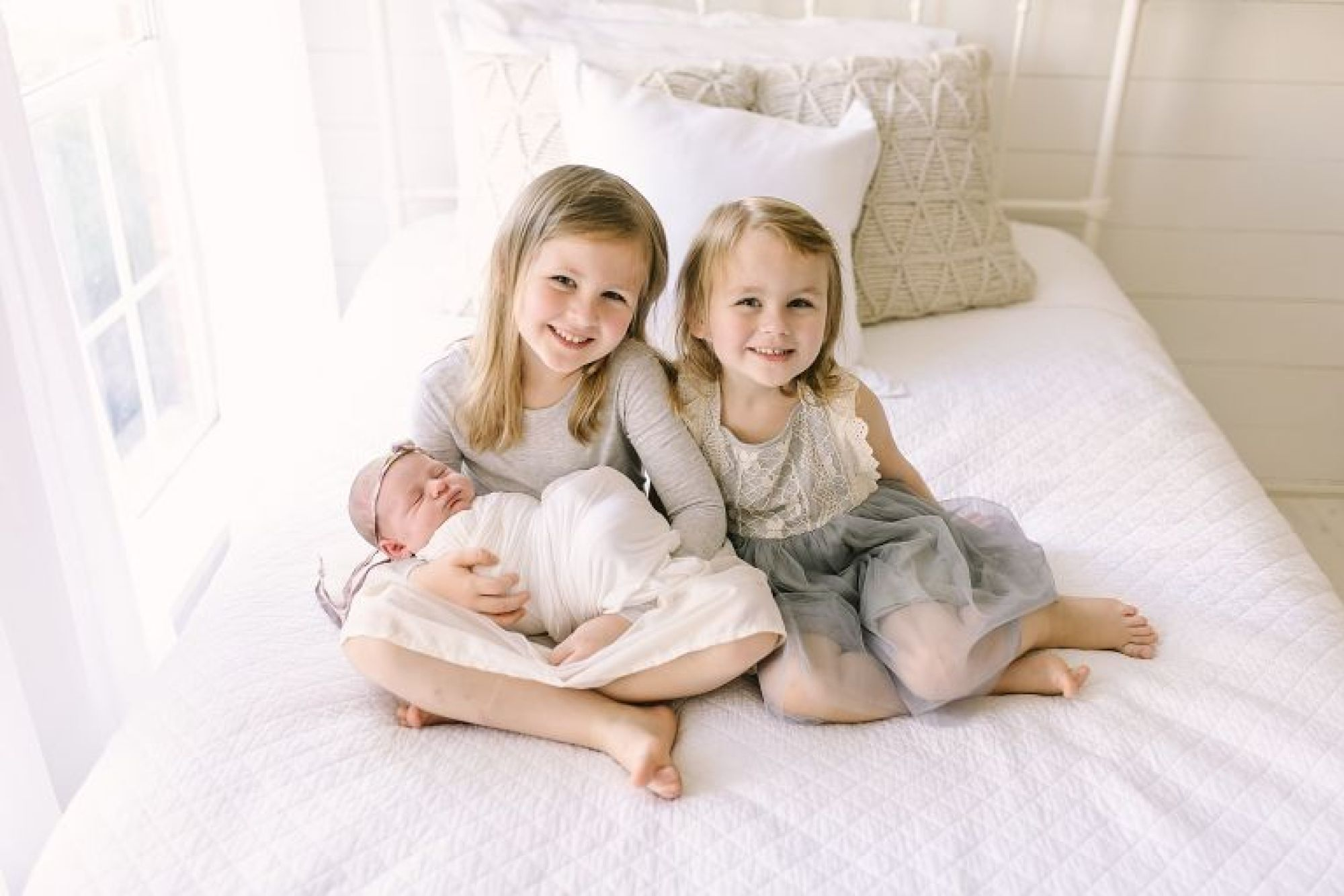 Two big sisters with newborn baby girl sitting on a bed in Courtney Griffin Photography's studio.