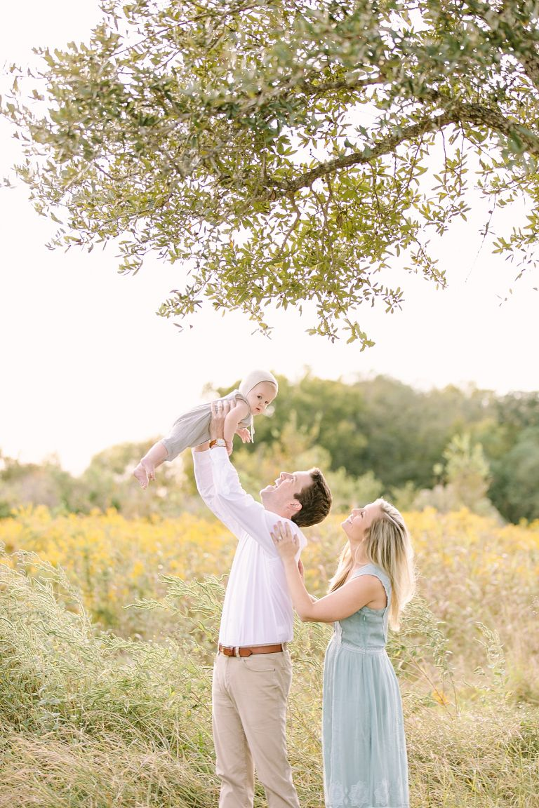 Daddy playing airplane with little boy in a beautiful field during family photoshoot with Houston Heights Family Photographer, Courtney Griffin Photography.