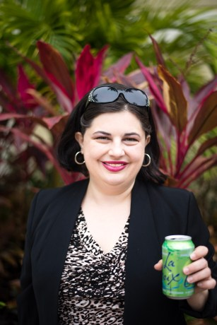 headshot of milli osburn outside, wearing a blazer, and holding a can of sparkling water.