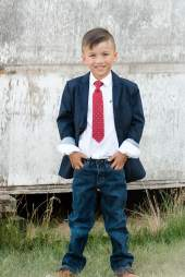 Boy in blue blazer with red tie on the farm