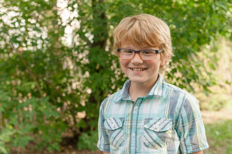 Boy with glasses in greenery