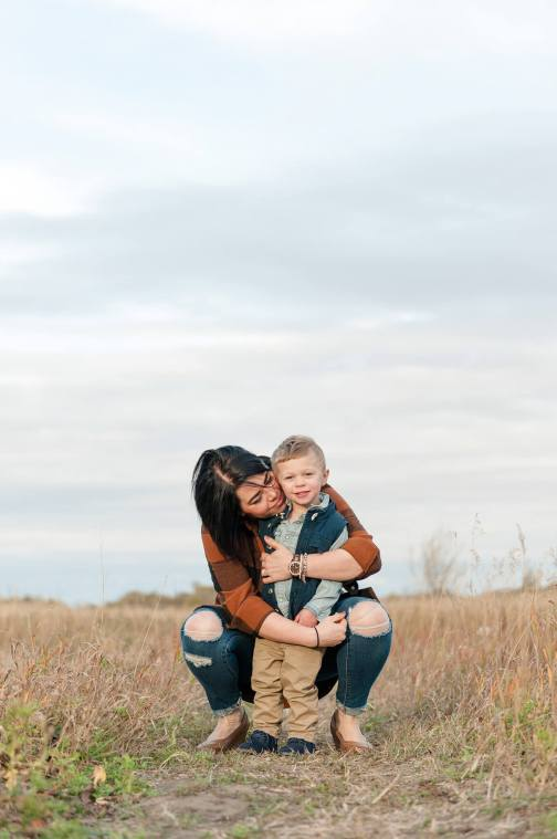 Mother cuddling with her toddler in field in the Lumsden valley