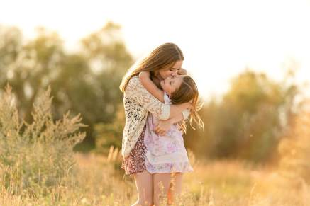 Sisters hugging at sunset in the tall grass