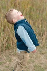 Three year old boy laughing at geese as they fly overhead