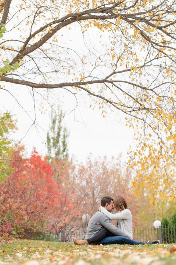 Couple sitting on the grass in fall surrounded by leaves