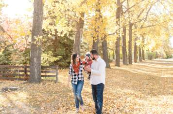 Family of three walking through treed lane in fall