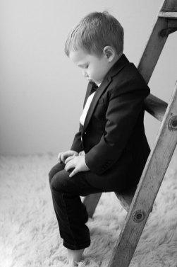 Little boy in suit on a ladder