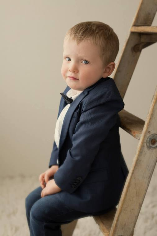 Little boy in suit sitting on a ladder