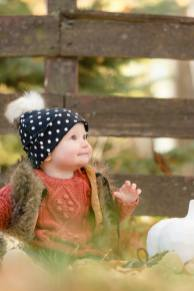 Little girl in hat and vest sitting with white pumpkin