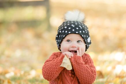 Little girl in polka dot pom pom hat