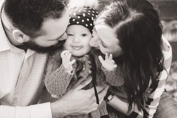 Mom and dad squishing little girls face with kisses