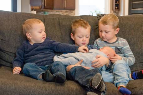 Three older brothers sit with new little brother on the couch