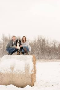 Couple on top of a round bale with their Bernese Mountain dog