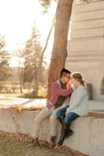 Couple sit together on cement wall in fall sunlight