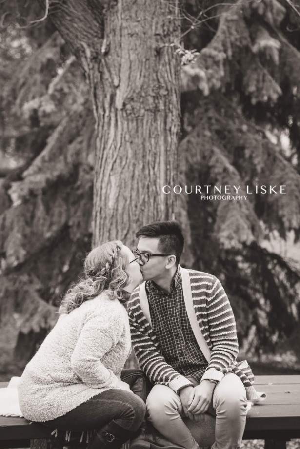 Kevin & Darriane kiss on a picnic table in Wascana Park