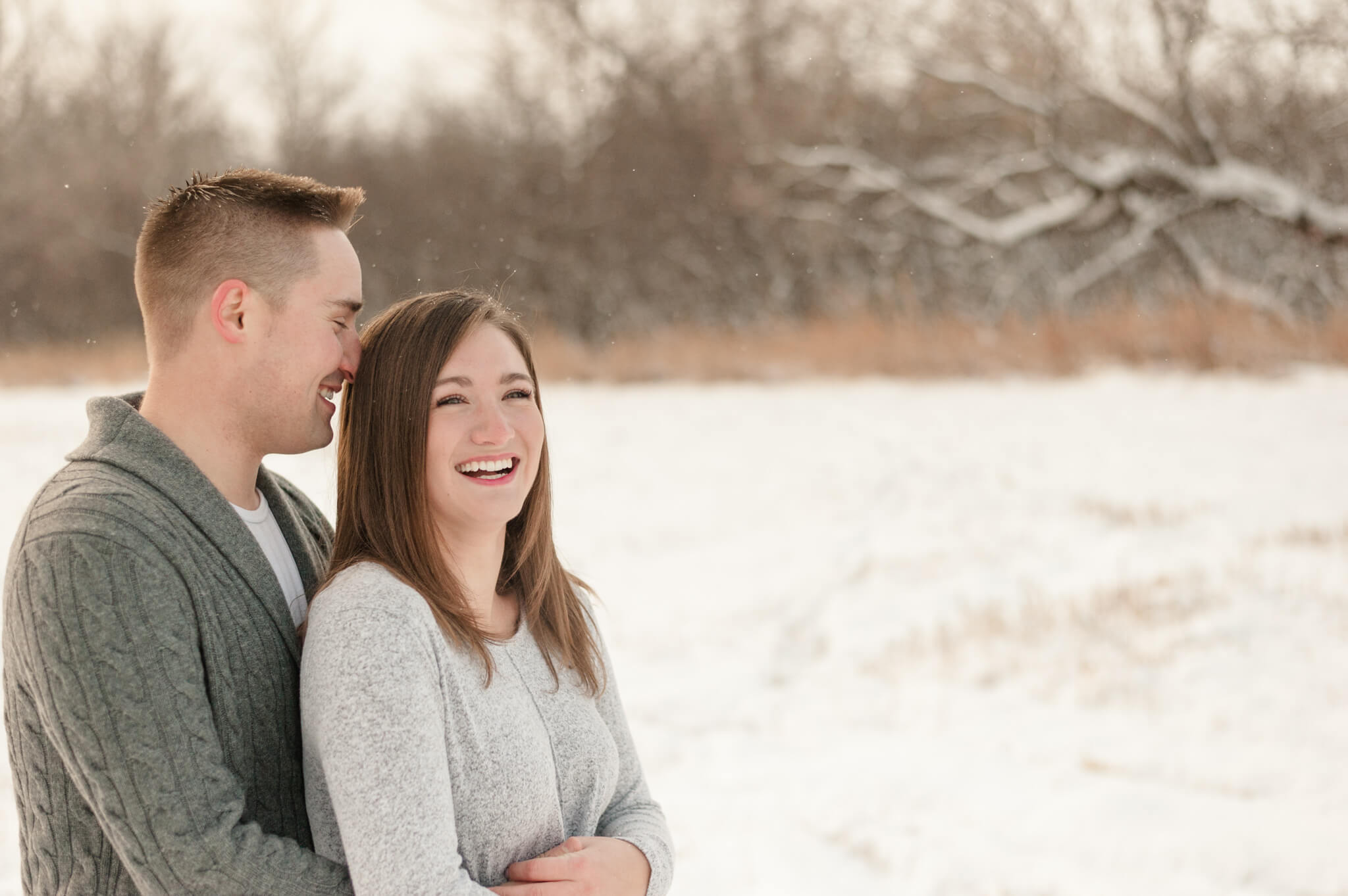 Man in grey sweater holds his fiancee in her white sweater