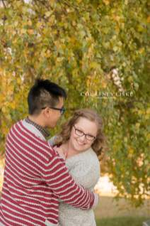 Man in red and white sweater snuggling with his fiancee