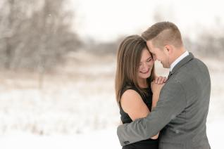 Woman in black dress and man in grey suit in the snow