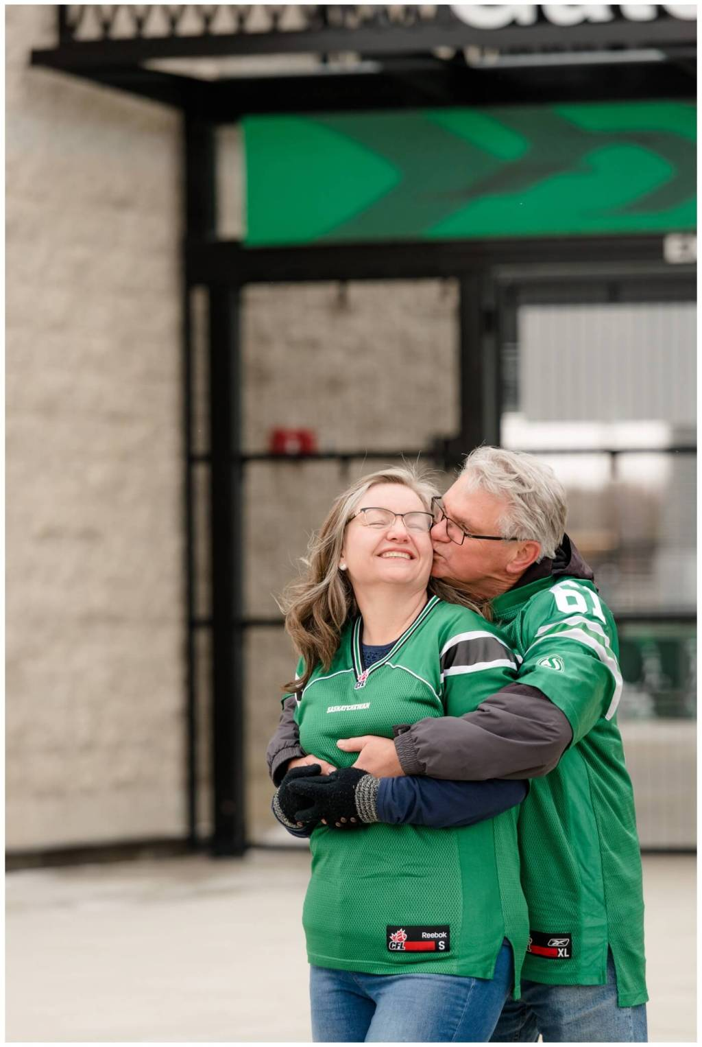 Regina Family Photographer - Fahlman Family - Marilyn-Mike - Rider Pride - Family Session - Kisses at Mosaic Stadium