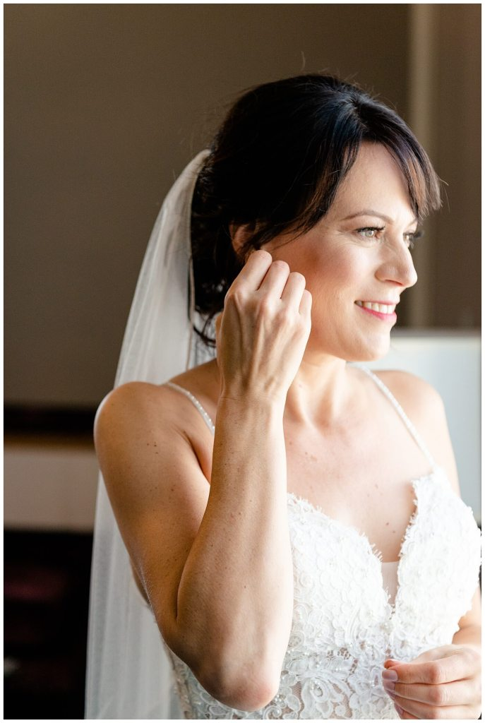 Scott & Keely - Regina Wedding - Bride putting in earring