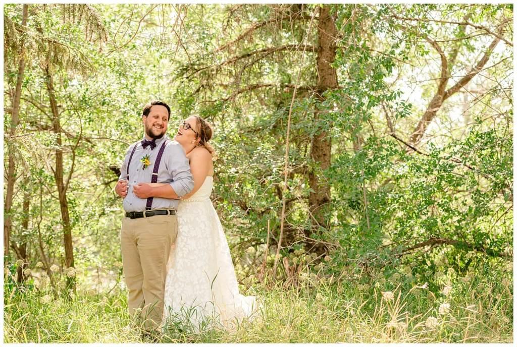 Regina Wedding Photographers - Ryan - Aeliesha - Bride stands behind her groom amongst the trees